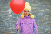 Smiling little girl with red balloon — Stock Photo