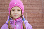 Leende liten flicka i rosa kappa — Stockfoto