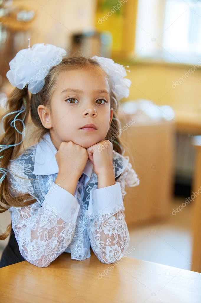 悲伤的小女孩坐在桌