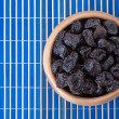 Dried prunes in wooden bowl - Stock Photo