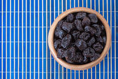 Dried prunes in wooden bowl — Stock Photo