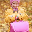 Smiling little girl in yellow coat with pink backpack — Stock Photo #24779617