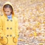 Sad beautiful girl in yellow jacket — Stock Photo #24779629