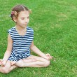 Girl in striped vest sits in lotus position — Stockfoto