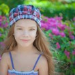 Little girl in green summer city park — Stockfoto