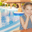 Little girl in striped vest near resort's pool — Stock fotografie