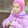 Little sad girl in pink coat — Stock Photo