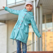Little girl in blue coat walking on curb - Stok fotoraf