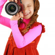 Smiling little girl in red dress with camera — Stock Photo