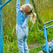 Little girl hanging on old exercise equipment - Stok fotoğraf