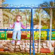 Little girl on swing in children&#039;s city park - Photo