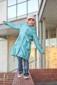 Little girl in blue coat walking on curb — Stock Photo