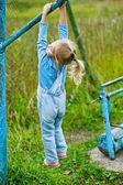 Little girl hanging on old exercise equipment — Stock Photo