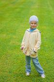Klein meisje permanent op groene gazon — Stockfoto