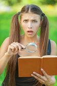 портрет серьезные красивая женщина лупа книга — Стоковое фото