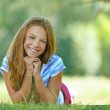 Teenage girl in blue blouse lying on grass — Stock Photo #25829959