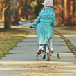 Stock Photo: Girl in blue cloak rides bicycle