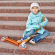 Girl with blue cloak with scooter — Stock Photo