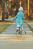Girl in blue cloak rides bicycle — Stock Photo