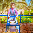 Little girl on swing in children's city park — Stock Photo