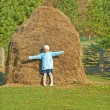 Smiling girl stands near haystacks — Stock Photo