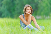 Young woman sitting grass — Stock Photo