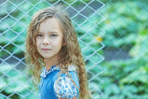 Smiling little girl with curly hair near fence of grid — Stock Photo
