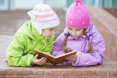 Two little girls in coats reads book — Stock Photo
