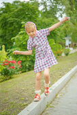 Little girl oscillates on curb — Stock Photo