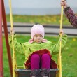 Mom rolls daughter on swing — Stock Photo