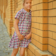 Little girl snear brick wall — Stock Photo
