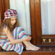 Little girl sitting near window — Stock Photo