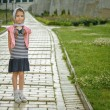 Little girl in jacket on sidewalk — Stock Photo