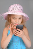 Little girl reading sms on cell phone — Stock Photo