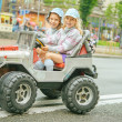 Two little girls riding toy car — Stock Photo