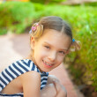 Little girl in green summer city park — Stock Photo