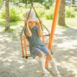 Little girl on swing in children's city park — Foto de Stock