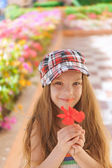 Beautiful smiling girl holding red flower — Stock Photo