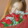 Stock Photo: Smiling little girl with bouquet of roses