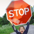 "Stock Photo: Little girl holding red sign ""STOP"""
