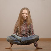 Little girl in lotus position is on hands — Stock Photo