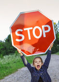 """Little girl holding a red sign """"STOP"""" — Stock Photo"""