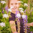 Little girl walks on blossoming meadow — Stock Photo #30301735