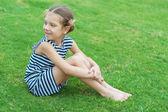 Beautiful smiling girl sitting on green grass — Stock Photo