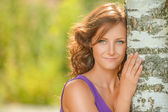 Cute dark-haired woman near birch tree — Stock Photo