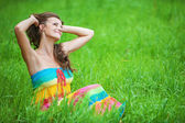 Woman in colorful dress sitting on grass — Stock Photo