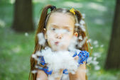 Dark-haired young woman blows cottonwood fluff — Stock Photo