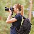 Smiling young woman photographs on camera — Foto de Stock