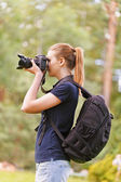 Smiling young woman photographs on camera — Stock Photo