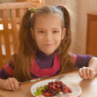 Smiling girl eating salad — Stock fotografie